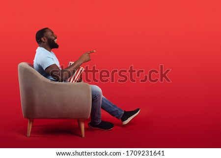 Amused televiewer sitting in the armchair at home while eating popcorns and watching a movie on red background Photo stock ©
