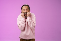 Amused thrilled gasping handsome happy bearded adult man in pink hoodie stooping screaming joyfully receive awesome incredible present standing speechless excited purple background