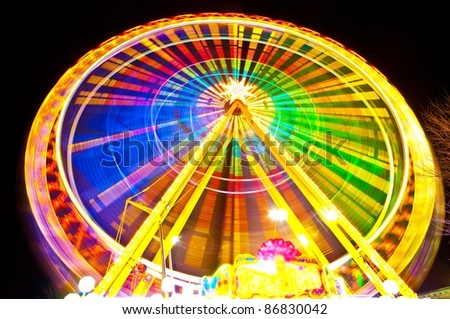 Amusement park at night background - ferris wheel in motion