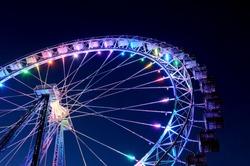 Amusement park at night - big ferris wheel with festive colorful illumination against blue evening sky.