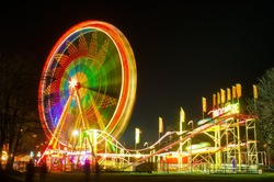 Amusement park at night - ferris wheel and rollercoaster in motion