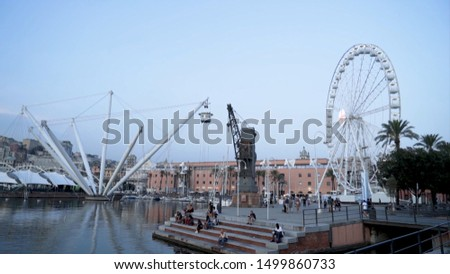 Amusement park with ferris wheel is located on pier. Action. Tourists walk through amusement park in sea bay in cloudy weather #1499860733