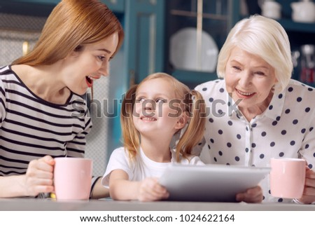 Amusing content. Pretty little girl sitting at the kitchen counter and showing her mother and grandmother a funny video while the women laughing amusingly