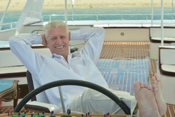 Amusing elderly man have a ride in a boat on sea