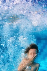 Amusing face portrait of smiling boy swimming and diving in blue pool with fun - jumping down underwater with splashes and foam. Family lifestyle and summer children water sports activity with parents