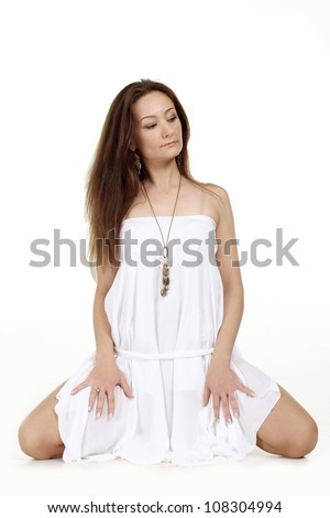 Amusing girl in a pretty white dress oa white background