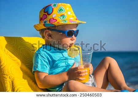 Amusing kid drinks juice from tubule against sea in sunny day