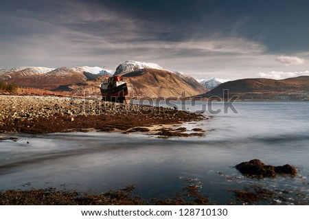 An abandoned boat ruin beached on the shores of Loch Linneh with Britain's tallest mountain, Ben Nevis, in the background