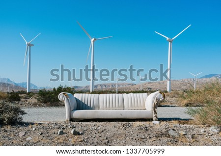 An abandoned couch in front of wind turbines