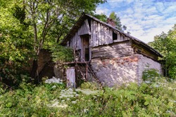 An abandoned dilapidated old house with a wooden attic and brick walls among thickets of wild grass and trees