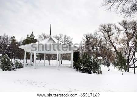 An abandoned empty gazebo in winter time at the city park.