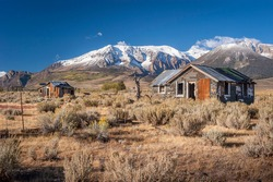An abandoned homesite in the Owens Valley of California with the snow covered Sierra Nevada mountain range in the background.