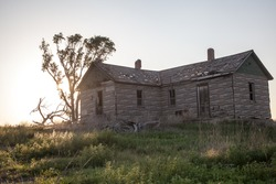 An abandoned homestead deteriorates over time in an open prairie