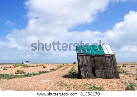 an abandoned leaning shack on a shingle beach