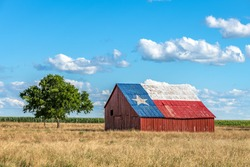 An abandoned old barn with the symbol of Texas painted on the roof sits in a rural area of the state, framed by farmland.