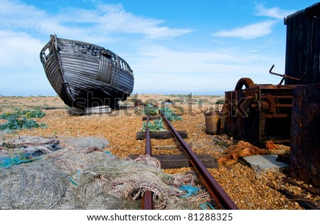 an abandoned old fishing boat surrounded by nets, rope and a railway line