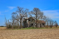 An abandoned old house completely surrounded by farmland.