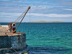 An abandoned, rusting steel crane and winch at the side of a pier in Portrush, Northern Ireland, UK - taken on a sunny day in summer with blue sky and turquoise water.