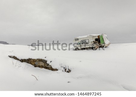 An abandoned RV sitting in a snowy field during a snow storm, Montgomery County, NY, USA. Stock fotó ©