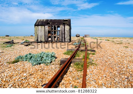 an abandoned shack on a shingle beach and an old railway line
