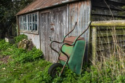 An abandoned shed with a broken window, green rusting wheelbarrow propped against the shed