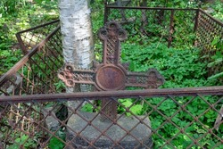An abandoned unknown grave with a rickety forged cross and a fence. Smolensk Lutheran Cemetery, Saint Petersburg, Russia
