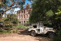 An abandoned vehicle stands beside a derelict building at the old silver mine at Argentella in Corsica