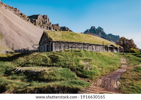 An abandoned vikings village. Sod rooftops, turf rooftops. Village located at the bottom of a high mountain i n Iceland. Around the farm a wooden fence. Traditional Scandinavian ancient architecture. Foto stock ©