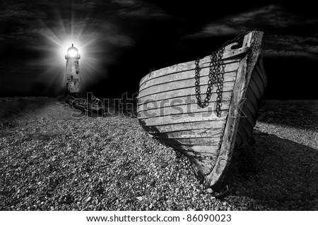 an abandoned wooden fishing boat on a shingle beach illuminated at night by the beam from a lighthouse in black and white