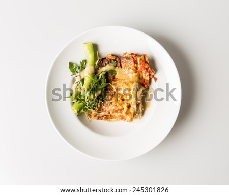 An above view of a dinner or lunch plate with the Italian pasta dish, lasagne and a small vegetable salad on the side as garnish.