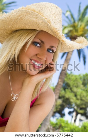 An absolutely gorgeous blond haired blue eyed young woman sits in front of  palm trees laughing 5a2db4bde76c