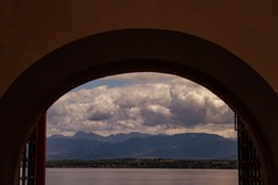 An abstract artistic sunset image of a landscape view of Lake Geneva, Switzerland through an arched window. There are houses, Alpine mountains, farms and rural areas across the lake. Sky is cloudy.