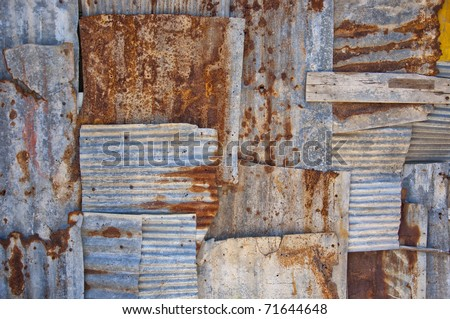 An abstract background image of rusty corrugated iron sheets overlapping to form a wall or fence.