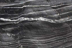 An abstract background image of the undulating layers of slate and marble on a geological cliff face