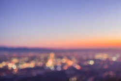 An abstract blurry image of a city skyline at sunset, featuring round bokeh balls from the twinkling lights below. View from Potato Mountain in Claremont Wilderness Park near Los Angeles California