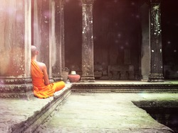 An abstract fantasy photograph of a Buddhist monk meditating in Angkor Wat temple in Siem Reap Cambodia