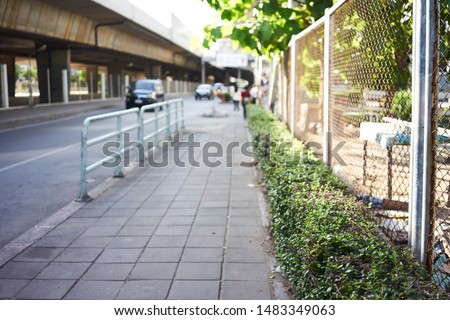 An abstract footpath, walkway, and bushes and fence in focus with blurry cars and blurry people. There are bright sunlight shining at the tree bush.