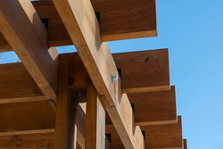 An abstract geometric composition of brown wooden planks against a blue sky. Fragment of an outdoor gazebo. Selective focus.