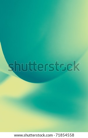 an abstract macro photo of curve shapes made up of paper, coloured in green-blue