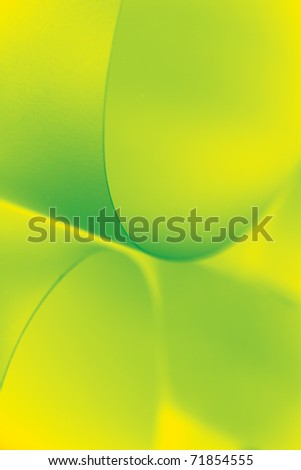 an abstract macro photo of curve shapes made up of paper, coloured in yellow and green
