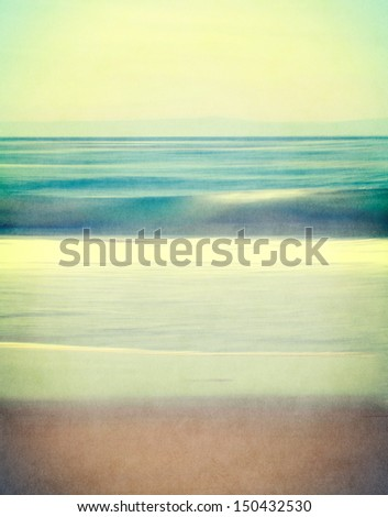 An abstract ocean seascape with blurred panning motion.  Image displays a retro, vintage look with cross-processed colors and a finely textured paper grain.
