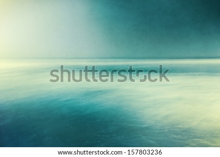 An abstract ocean seascape with blurred panning motion.  Image displays a retro, vintage look with cross-processed colors and a pleasing paper grain and texture.