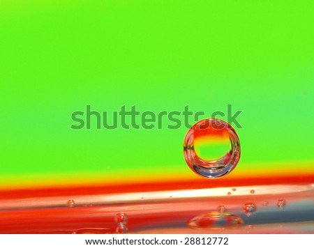 An abstract photo portraying a single bubble bouncing along a colorful line against a green background