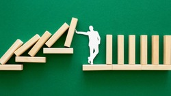 An abstract representation of the financial crisis. man trying to stop blocks from falling on him
