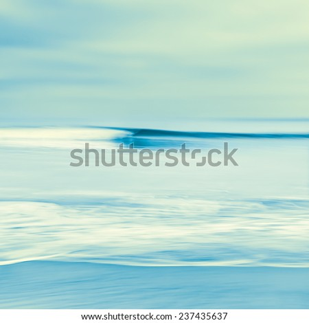 An abstract seascape with blurred panning motion.  Image displays blue and yellow cross-processed colors.