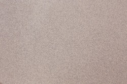 An abstract tan background with gray speckles throughout.
