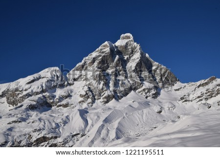 An abundantly snow-covered Matterhorn seen from the Italian side. Typically winter landscape, panorama from the ski slopes at the foot of the mountain on the border between Italy and Switzerland #1221195511