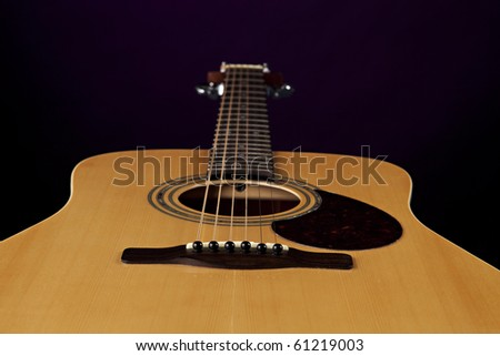 An acoustic natural color guitar isolated against a black background.