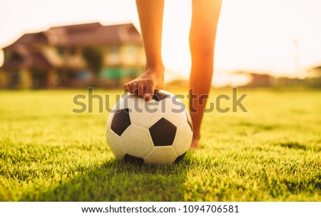 An action sport picture of a group of kid playing soccer football for exercise in before the sunset.
