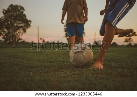 An action sport picture of a group of kids playing soccer football for exercise in community rural area under the sunset.